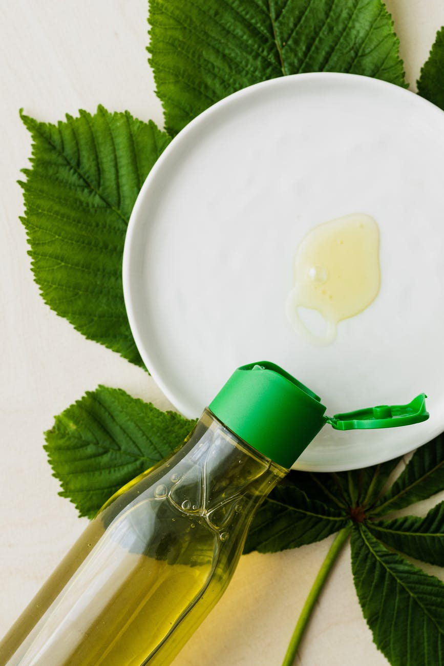 cosmetic oil in bottle and on white plate